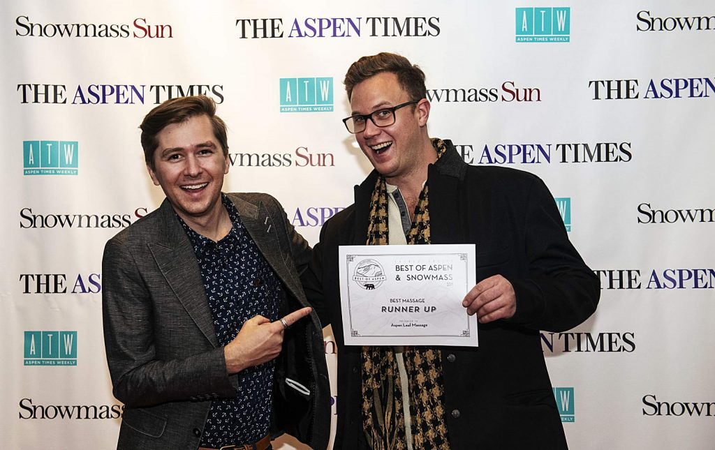 Paul Woznicki, left, points to Travis Andrews' award for Best Massage during the Best of Aspen and Best of Snowmass Party at The Wheeler on Wednesday, October 23, 2019. (Kelsey Brunner/The Aspen Times)