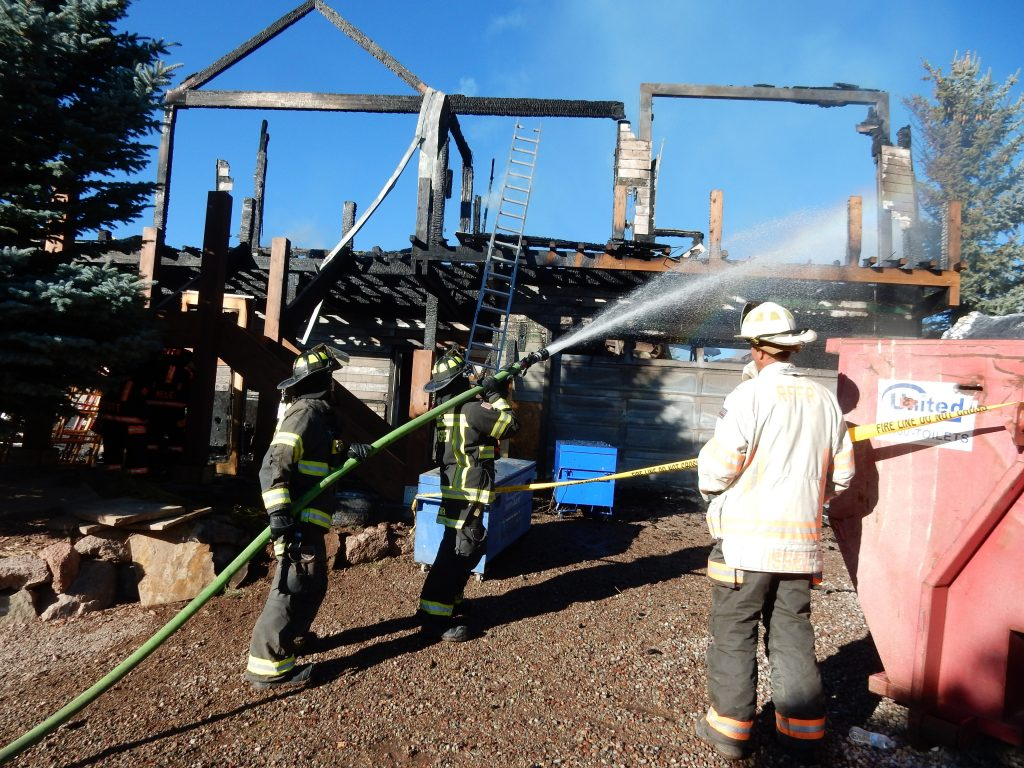 Firefighters douse charred, smoldering remains of a house in Missouri Heights Tuesday. The 5,000-square-foot structure was a total loss.