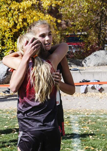 Darienne Kenny, left, hugs her older sister, Kylie Kenny, after Kylie won first place in the Varsity Girls division of the 2019 Chris Severy Cross Country Invitational at Aspen High School on Saturday, October 5, 2019. (Kelsey Brunner/The Aspen Times)