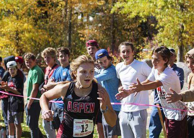 Stella Sherlock runs past cheering Aspen High School students to cross the finish line during the Chris Severy Invitational in Aspen on Saturday, October 5, 2019. (Kelsey Brunner/The Aspen Times)