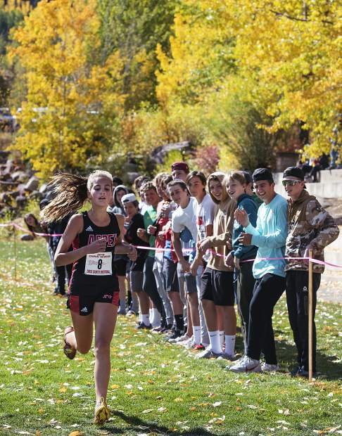 Kylie Kenny crosses the finish line to the applause of other Aspen High School students during the 2019 Chris Severy Cross Country Invitational in Aspen on Saturday, October 5, 2019. (Kelsey Brunner/The Aspen Times)