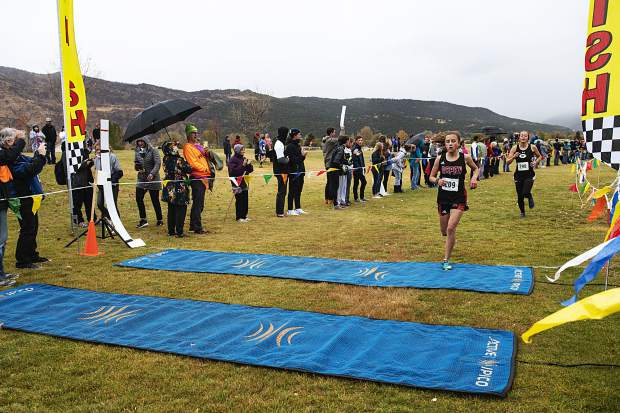 Aspen High School's Elsie Weiss crosses the finish line fourth closely followed by Gunnison High School's Ivy Pelletier during the regional meet at Crown Mountain Park in El Jebel on Friday, October 18, 2019. (Kelsey Brunner/The Aspen Times)