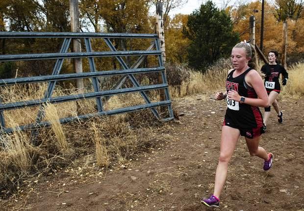 Aspen High School's Greta Hansen, left, and Montezuma-Cortez High School's Ridley Dennison compete in the varsity girls' regional meet at Crown Mountain Park in El Jebel on Friday, October 18, 2019. (Kelsey Brunner/The Aspen Times)