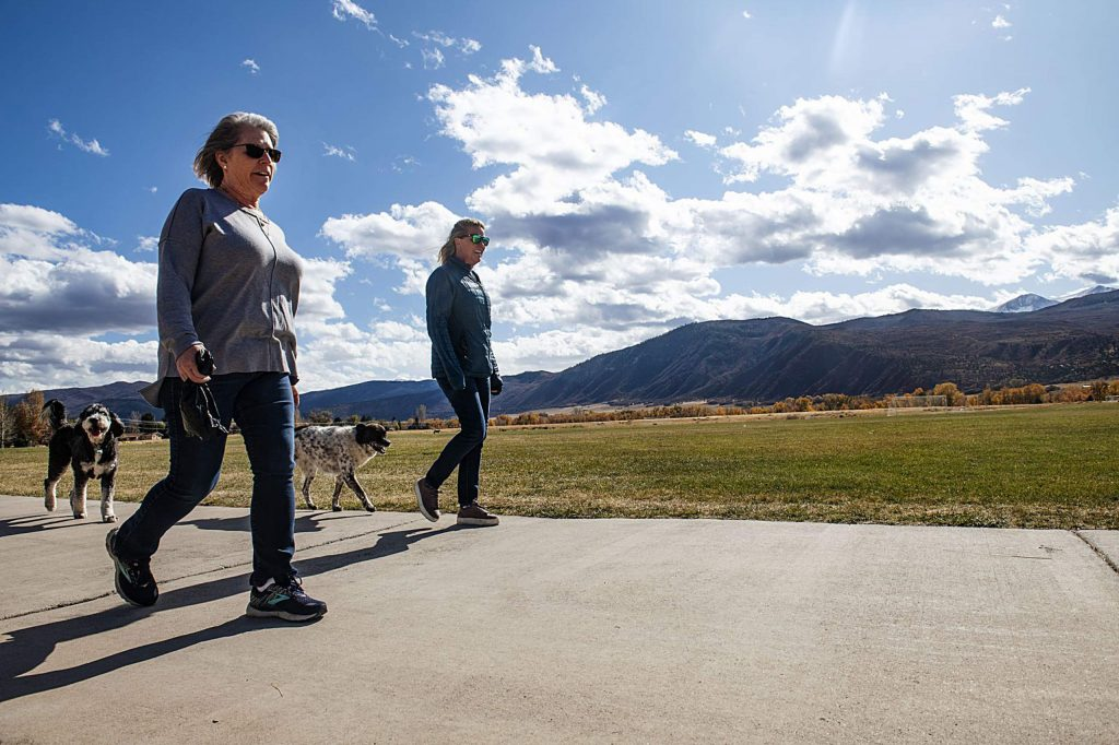 Debbie Wheatley, left, and Pam Foley walk their dogs around Crown Mountain Park on Tuesday. Voters approved a property tax hike last May to maintain and improve the popular park.