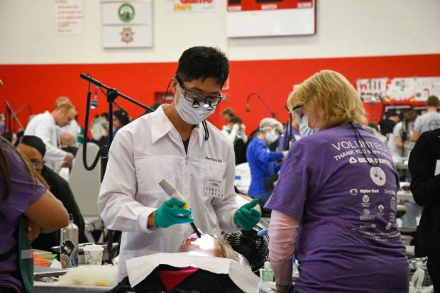 A dentist and volunteer work on a patient at the 2019 Western Colorado Mission of Mercy Free Dental Clinic at Glenwood Springs High School.