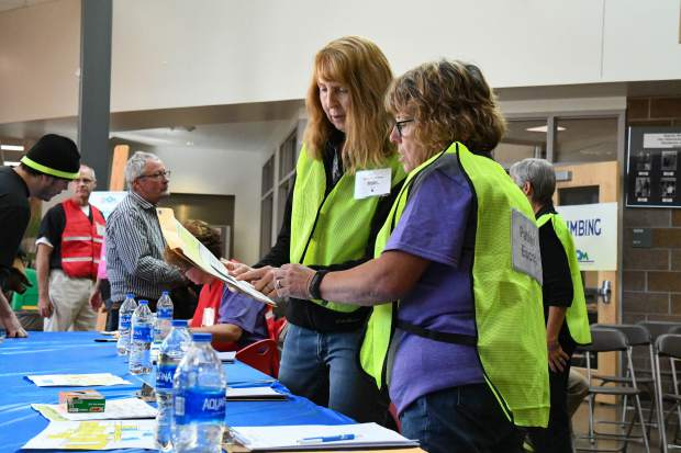 Volunteers Darlene James and Robin Van Norman speak about a patients information at the 2019 Western Colorado Mission of Mercy Free Dental Clinic at Glenwood Springs High School.