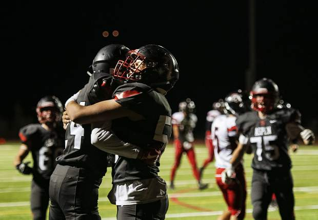 Aspen High School's Jon Woodrow (24), left, and Aidan Ledingham (56), right, hug after a touchdown was scored for the Skiers during the homecoming game against Grand Valley High School in Aspen on Friday, Sept. 27, 2019. (Kelsey Brunner/The Aspen Times)