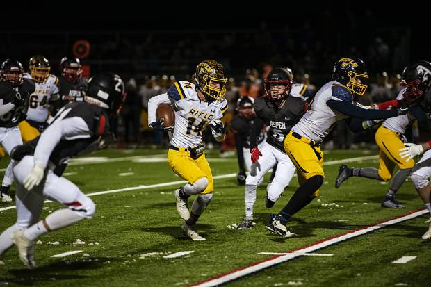 Rifle High School's Talon Cordova (14), center, runs the ball during the varsity game against Aspen High School on Friday, October 18, 2019. (Kelsey Brunner/The Aspen Times)