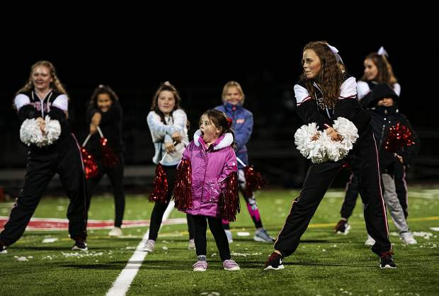 Olivia Glathar, 5, center, gives a big yawn as the Aspen High School Spirit Team leads the spirit campers in a halftime show at the varsity game against Rifle High School in Aspen on Friday, October 18, 2019. (Kelsey Brunner/The Aspen Times)