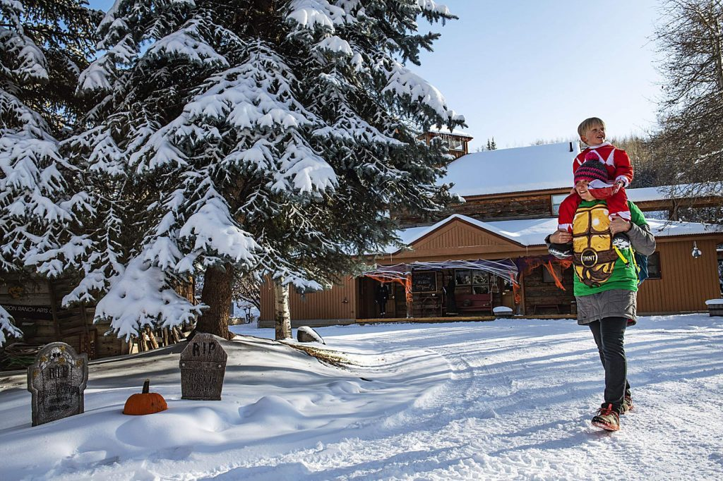 Ellen McCready carries her son Scott McCready, 3, on her shoulders to the next trick-or-treat spot at Anderson Ranch in Snowmass on Wednesday, October 30, 2019. (Kelsey Brunner/The Aspen Times)