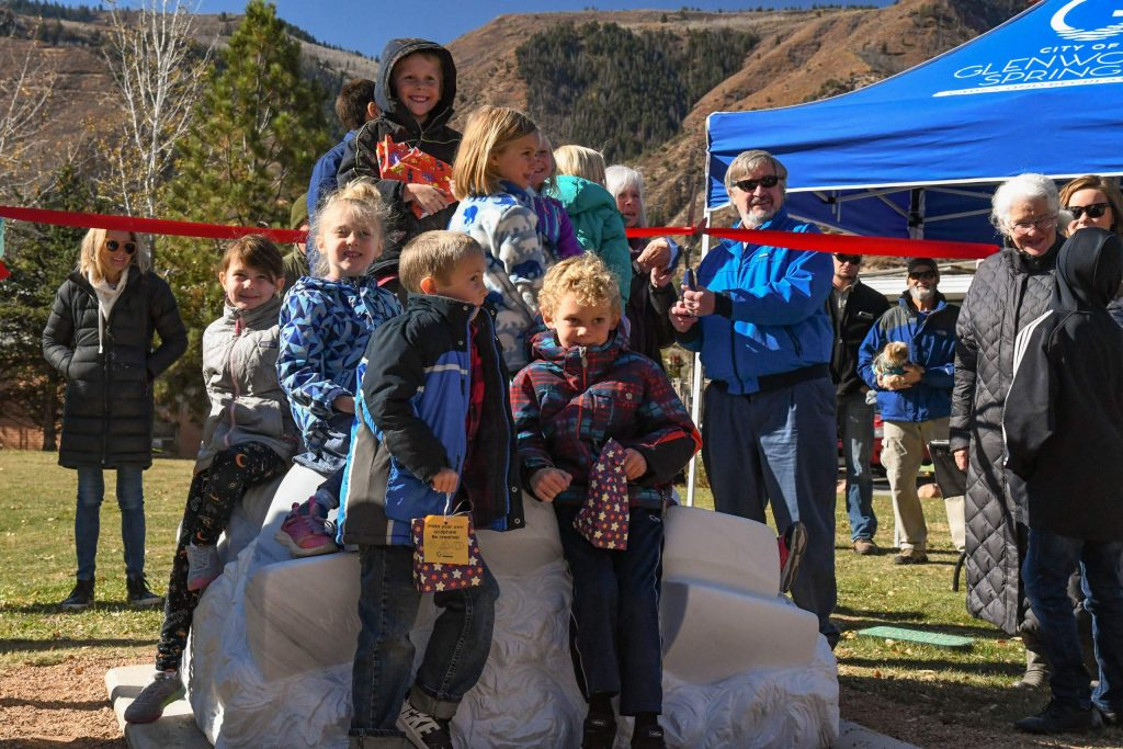Kids sit on top of the new Tubing on the Colorado sculpture while artist Madeline Wiener and Glenwood Springs City Councilor Charlie Willman cut the ribbon during the dedication ceremony on Friday morning.