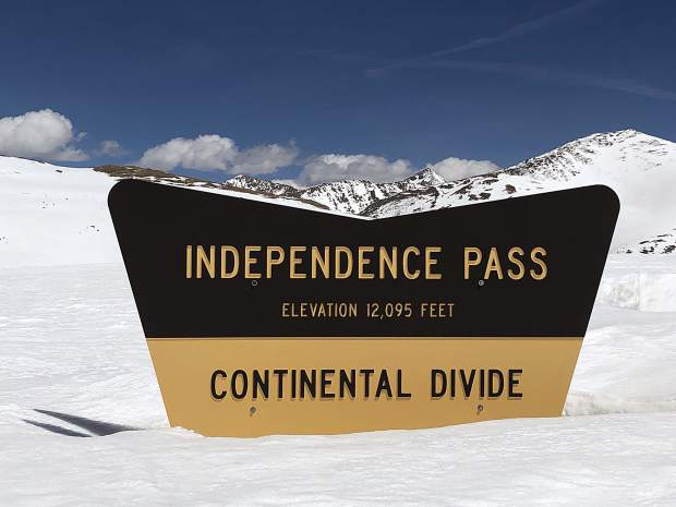 The summit sign for Independence Pass sticks up from the snow.