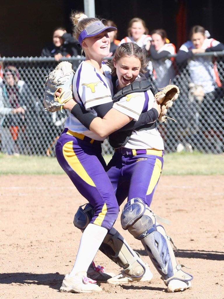 Basalt High School softball pitcher Maya Lindgren, left, hugs catcher Zoe Vozick after the team beat Lamar for the regional championship on Saturday, Oct. 19, 2019, on the BHS field. (Photo by Austin Colbert/The Aspen Times)