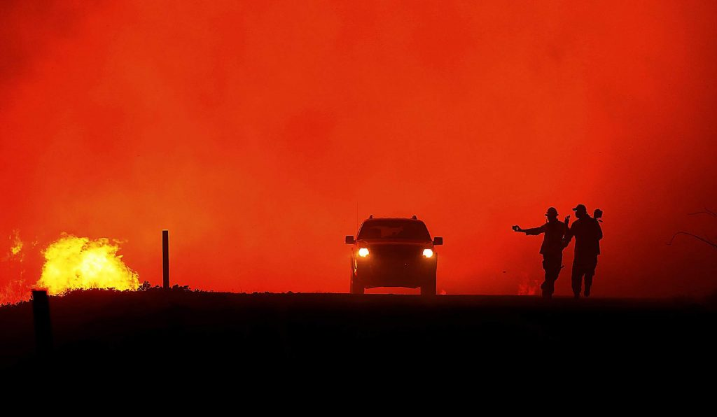 Photographers documenting the Kincade Fire run as the fire approaches the road, Oct. 24, 2019, in Sonoma County, Calif. (Kent Porter/The Press Democrat via AP)