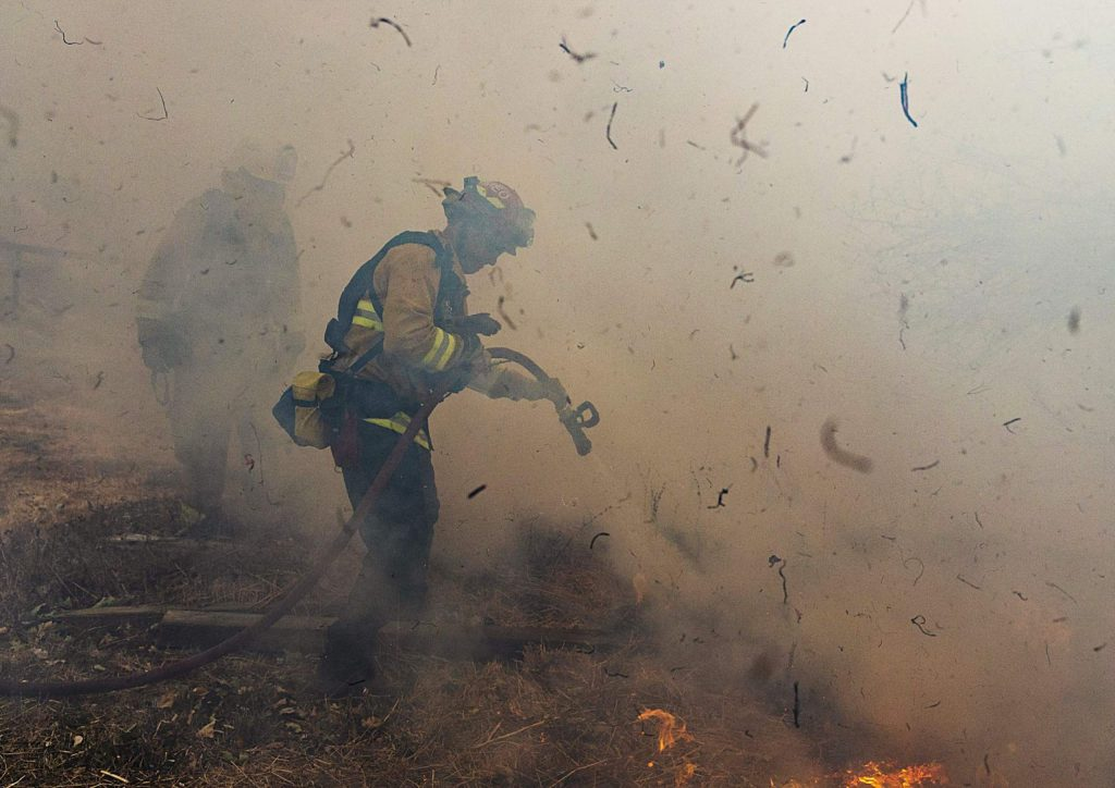 Firefighters from San Matteo work to extinguish flames from the Kincade Fire in Sonoma County, Calif., Oct. 27, 2019. (AP Photo/Ethan Swope)