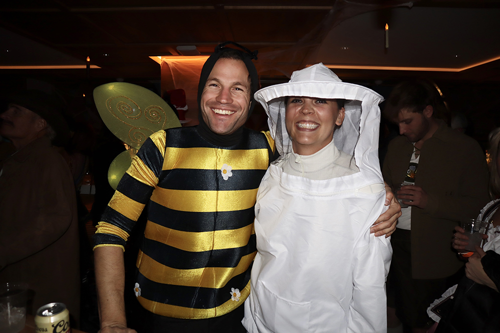 A honey bee and bee keeper away for the hive.