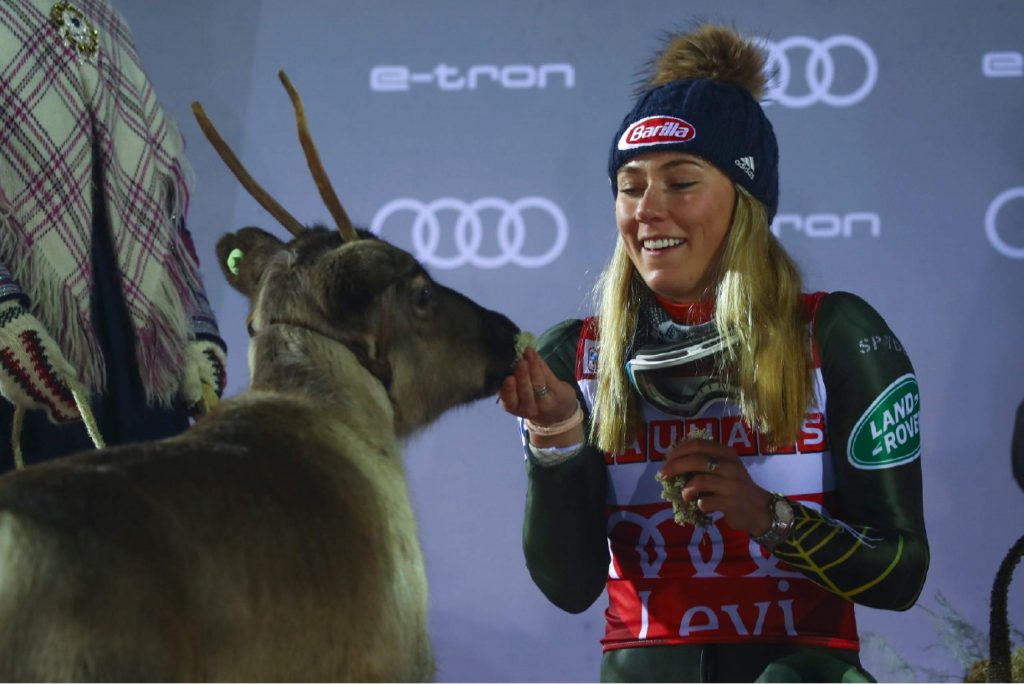 United States' Mikaela Shiffrin feeds a reindeer during the podium ceremony after winning an alpine ski, women's slalom in Levi, Finland, Saturday, Nov. 23, 2019. (AP Photo/Alessandro Trovati)