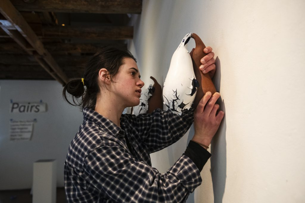 Digital Fabrication Lab Technician Leah Aegerter helps hang a coworker's ceramic pieces for the Pairs gallery at Anderson Ranch on Thursday, October 31, 2019. (Kelsey Brunner/The Aspen Times)