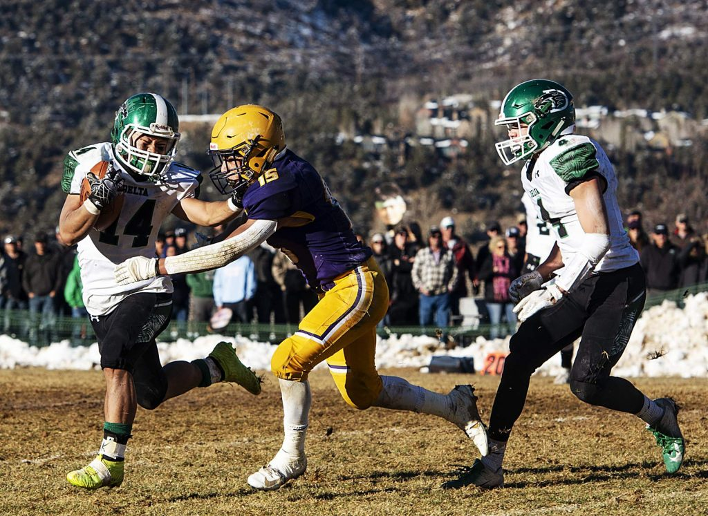 Delta High School's Ku Moo, left, runs the ball while Basalt High School's Rulbe Alvarado attempts to tackle during the semifinal game in Basalt on Saturday, November 23, 2019. (Kelsey Brunner/The Aspen Times)