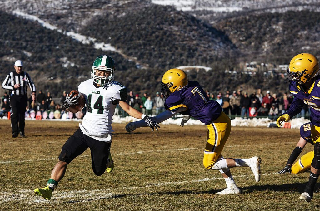 Delta High School's Ku Moo runs the ball in close pursuit by Basalt High School's Wilson Maytham during the semifinal game in Basalt on Saturday, November 23, 2019. (Kelsey Brunner/The Aspen Times)