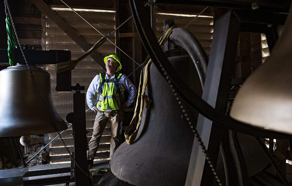 Sean Wooton looks up at the top of the belfry Friday after bringing the third new bronze bell into St. Mary Catholic Church in Aspen. One of the original bells, which is made of steel, will remain in the tower with the new bells.