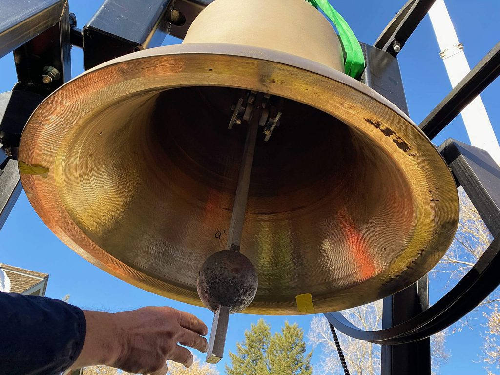 The largest of the new three bells for St. Mary Catholic Church is rung Friday by Fr. Darrick Leier before it gets lifted into the bell tower.