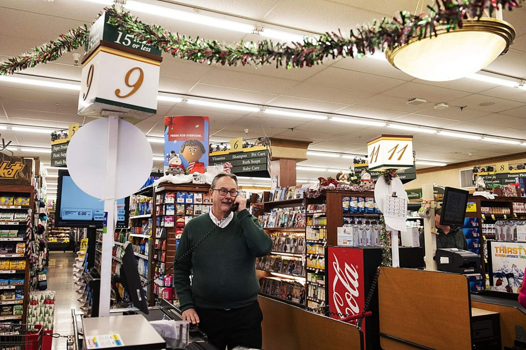 City Market general manager John Hailey takes a phone call at the front register in Aspen on Tuesday, November 12, 2019. Hailey officially retires on December 3. (Kelsey Brunner/The Aspen Times)