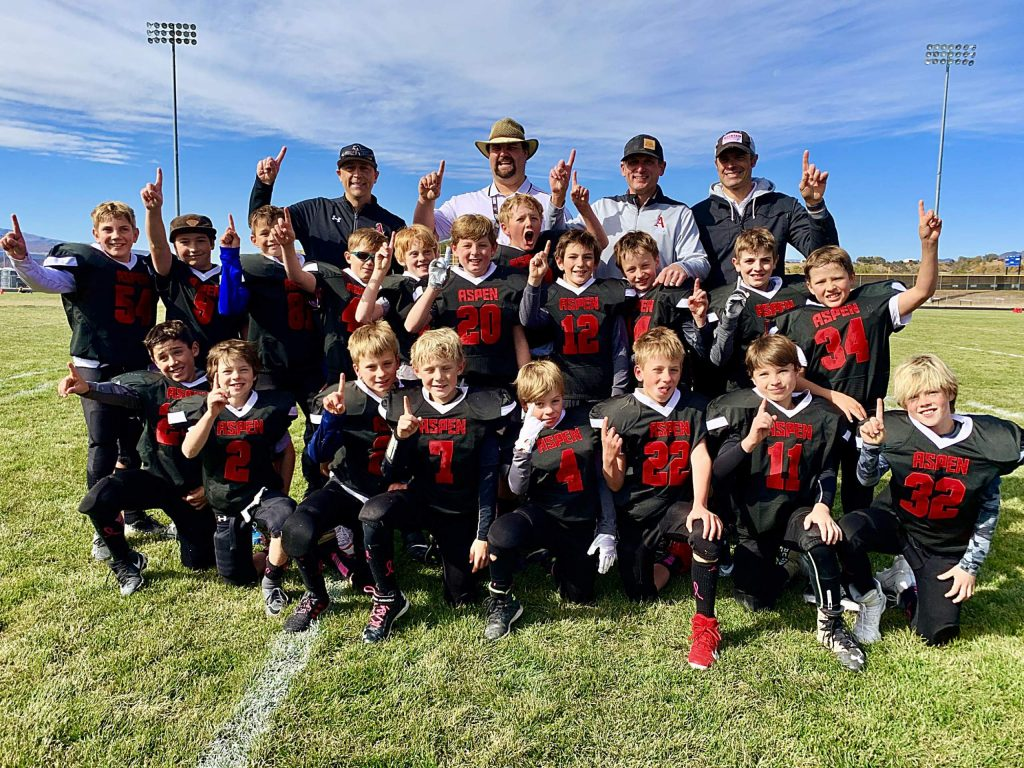The third- and fourth-grade Aspen football team celebrates after going undefeated (6-0) and winning the championship. The team's starting defense did not allow a single point scored.
