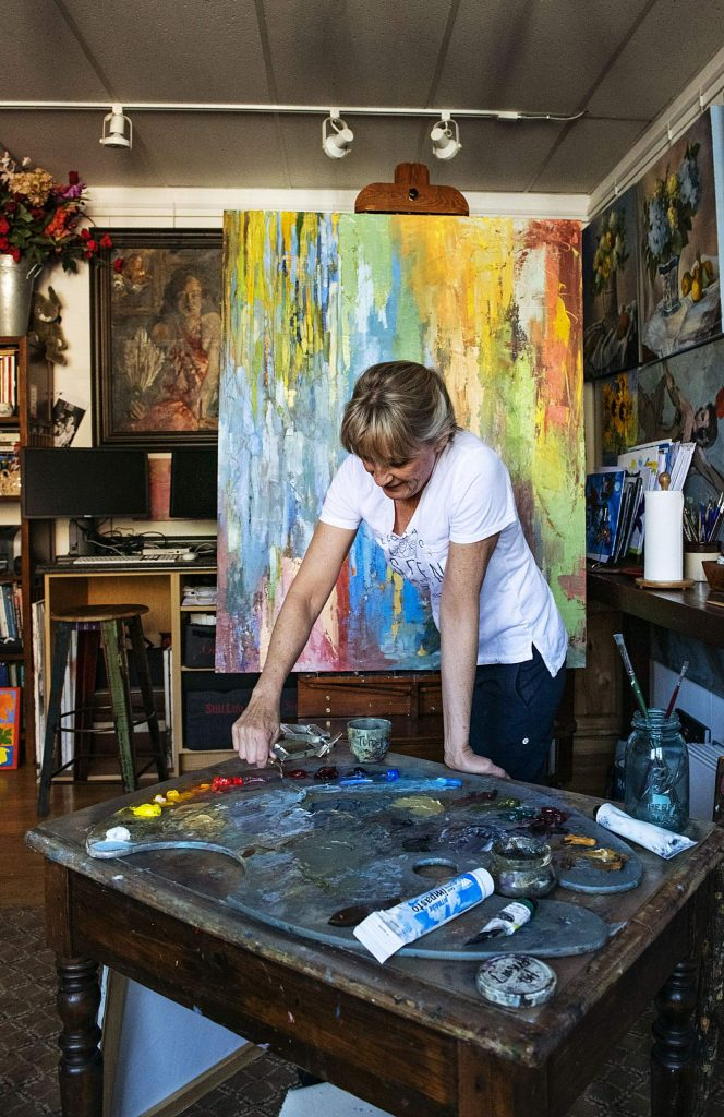 Lorraine Davis mixes oil paint to add to her large canvas in her studio at the Red Brick Center for the Arts in Aspen on Thursday, November 14, 2019. Davis created the piece using a palette knife, which she said was unusual for her. Davis's oil paintings explore everything from abstract to realism. She's been a resident at the Red Brick since 2013. (Kelsey Brunner/The Aspen Times)