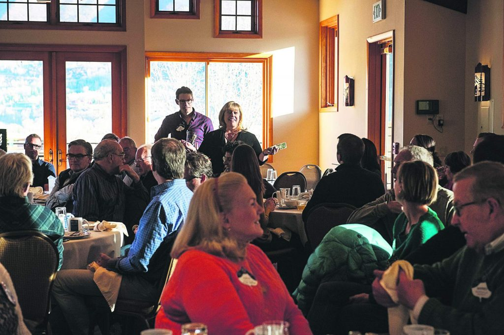 """Rotary members go around the room giving """"happy bucks"""" during the morning meeting in the Mountain Chalet on Thursday, November 7, 2019. Members donate money and share a positive thing with the group. (Kelsey Brunner/The Aspen Times)"""