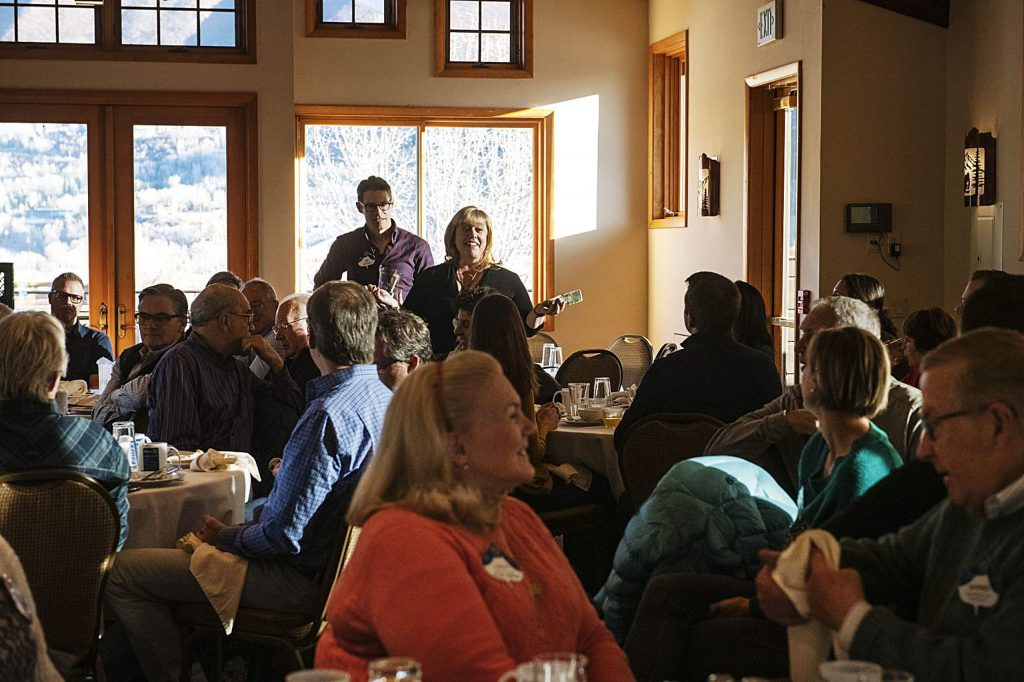 "Rotary members go around the room giving ""happy bucks"" during the morning meeting in the Mountain Chalet on Thursday, November 7, 2019. Members donate money and share a positive thing with the group. (Kelsey Brunner/The Aspen Times)"