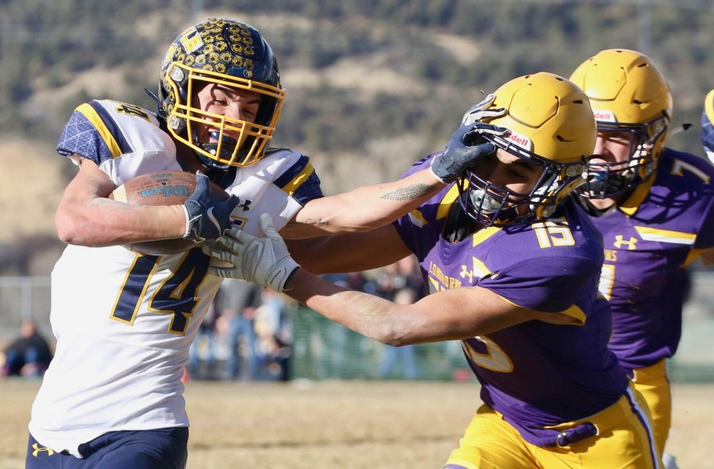 Basalt High School football's Rulbe Alvarado, right, tries to fend off a stiff arm from Rifle's Talon Cordova on Saturday, Nov. 16, 2019, on the BHS field. The Longhorns won the Class 2A state quarterfinal game in double overtime, 21-14. (Photo by Austin Colbert/The Aspen Times)