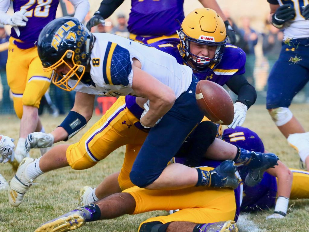 The Basalt High School defense knocks the ball away from Rifle runner Levi Warfel, who would recover the ball, on Saturday, Nov. 16, 2019, on the BHS field. The Longhorns won the Class 2A state quarterfinal game in double overtime, 21-14. (Photo by Austin Colbert/The Aspen Times)