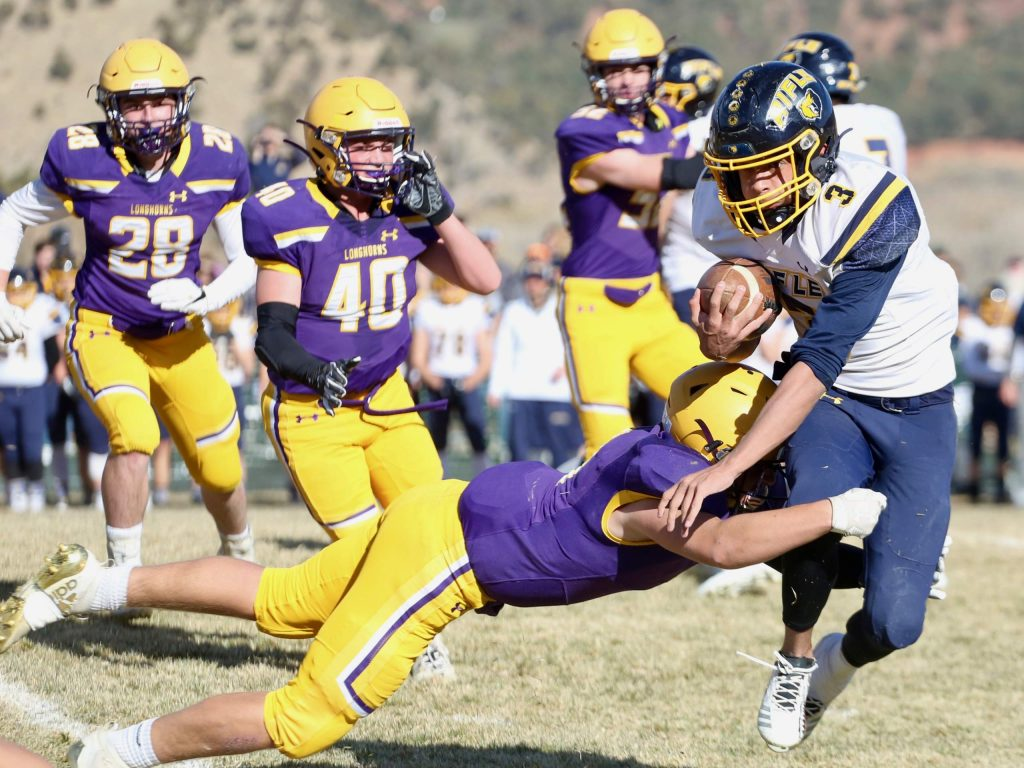 Basalt High School football's Sam Sherry goes in for a tackle on Rifle's Kenny Tlaxcala on Saturday, Nov. 16, 2019, on the BHS field. The Longhorns won the Class 2A state quarterfinal game in double overtime, 21-14. (Photo by Austin Colbert/The Aspen Times)