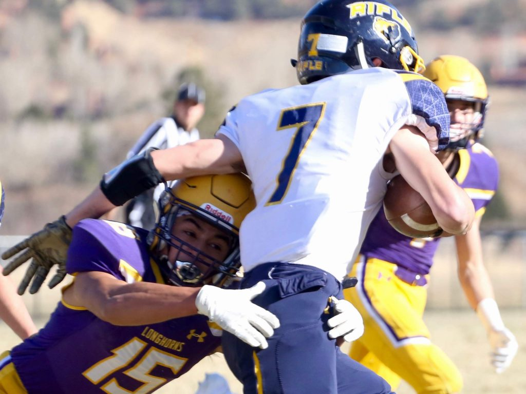 Basalt High School football's Rulbe Alvarado, left, makes a tackle on Rifle quarterback Holden Stutsman on Saturday, Nov. 16, 2019, on the BHS field. The Longhorns won the Class 2A state quarterfinal game in double overtime, 21-14. (Photo by Austin Colbert/The Aspen Times)