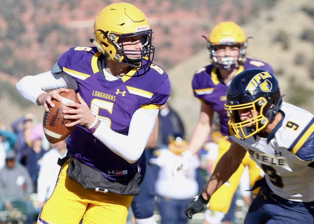 Basalt High School quarterback Matty Gillis looks to evade a Rifle defender on Saturday, Nov. 16, 2019, on the BHS field. The Longhorns won the Class 2A state quarterfinal game in double overtime, 21-14. (Photo by Austin Colbert/The Aspen Times)