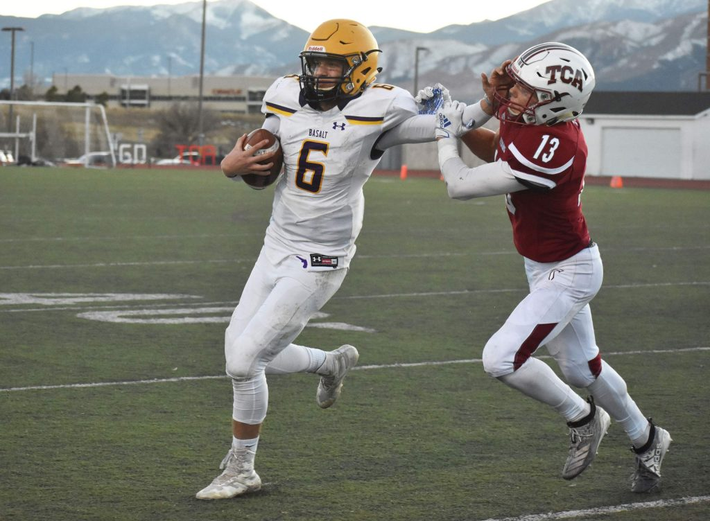 Matty Gillis stiff arms a TCA defender during a 2A playoff game. The Longhorns defeated the Titans 13-7 on Saturda,y Nov. 10, 2019 in Colorado Springs to advance to the second round of the playoffs. (Lindsey Smith, The Gazette)
