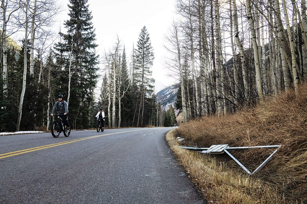 Two bicyclists ride past half of the damaged Maroon Creek Road gate Tuesday. (Kelsey Brunner/The Aspen Times)