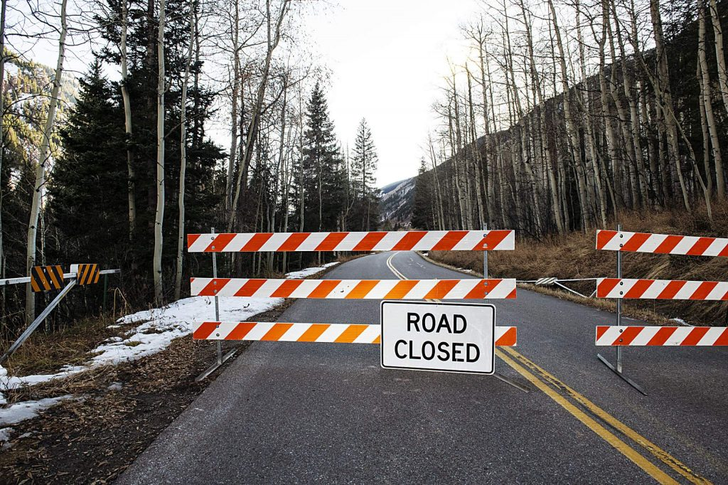 Half of the winter closure gate on Maroon Creek Road lies in the ditch beside the road Tuesday after a car crashed into it and inadvertely opened the closed road to traffic. (Kelsey Brunner/The Aspen Times)