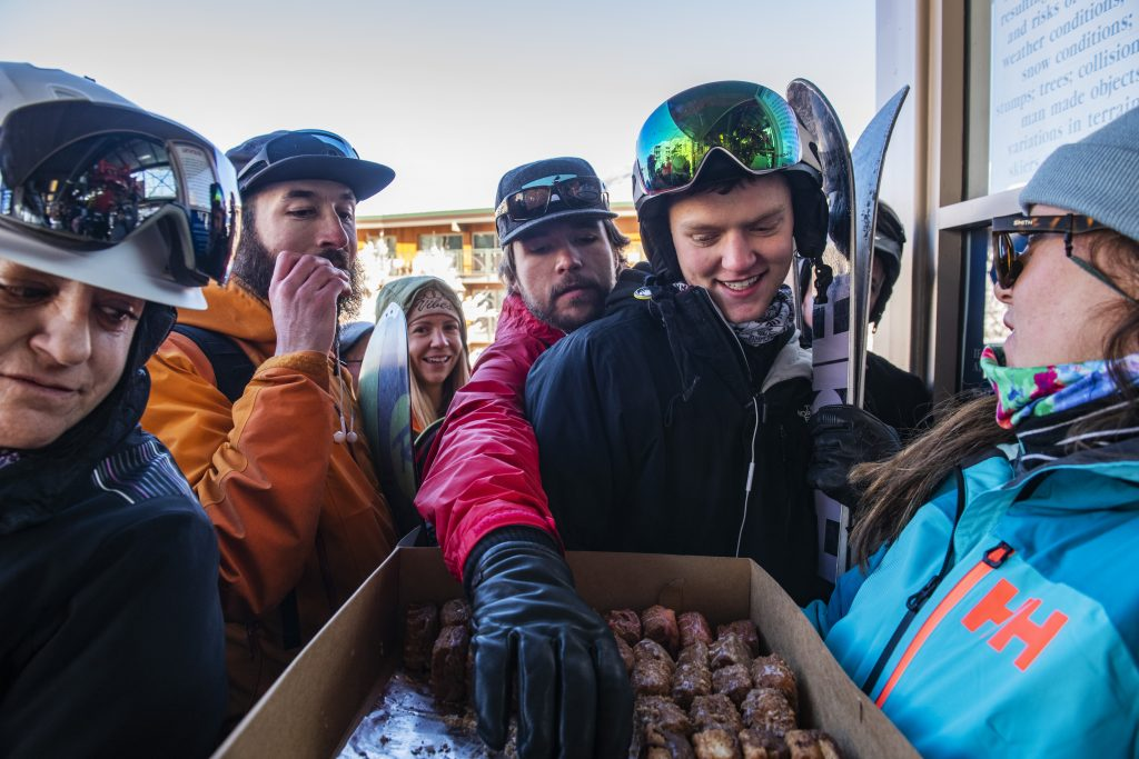 Skier Paul Crouse, right, was the first in line Saturday then joined by his buddy Rob Skorr (red jacket). They were treated to doughnuts as they wait for the Silver Queen Gondola to open at Aspen Mountain.