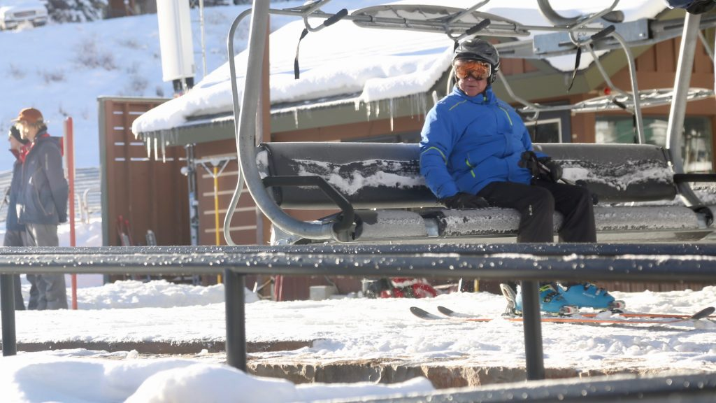 One of the first skiers of the season gets on the Village Express chairlift during Snowmass Ski Area's opening day on Saturday, Nov. 23, 2019. (Photo by Austin Colbert/The Aspen Times)