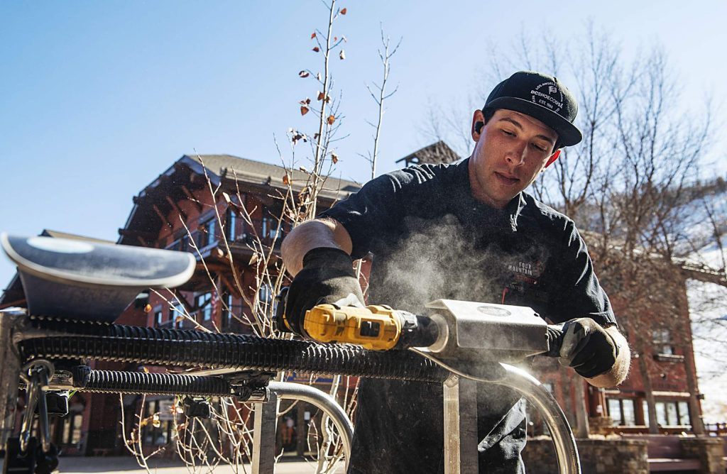 James Lohbauer performs a brushing process to the bottom of skis freshly treated with Phantom, an alternative to wax, outside of the Aspen Highlands tune shop on Wednesday.