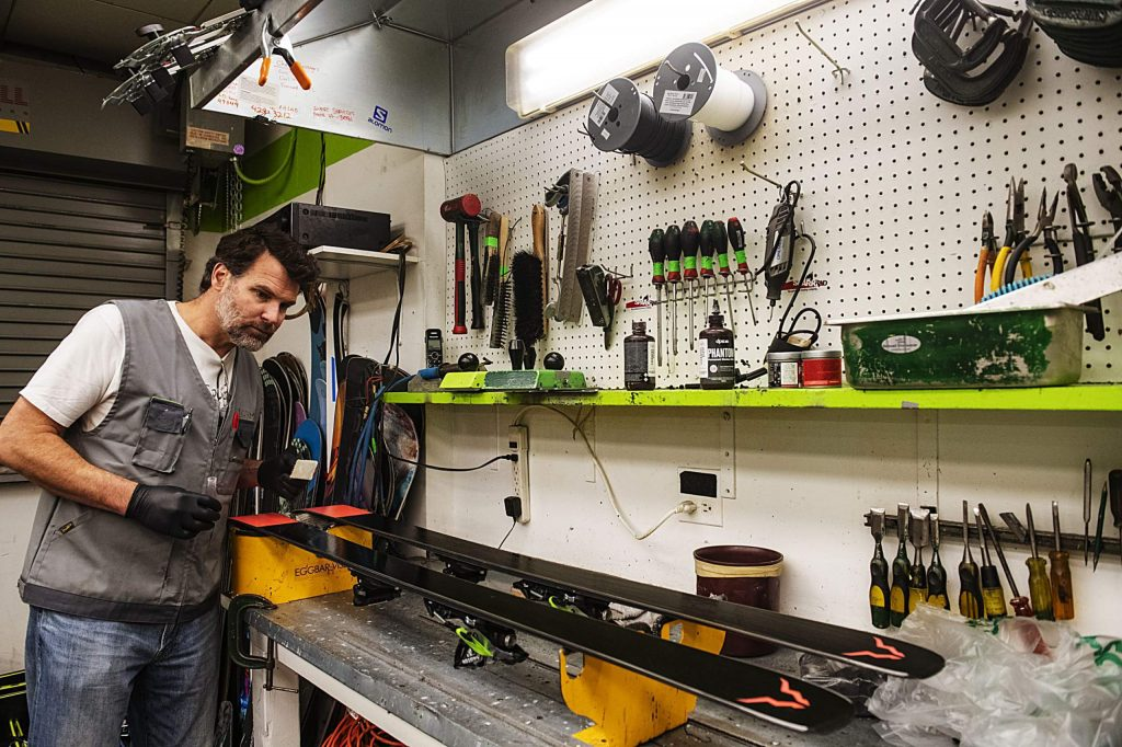 Aspen Skiing Company Tune Manager John Norman examines the bottom of the skis after applying Phantom in the Highlands tune shop on Wednesday.