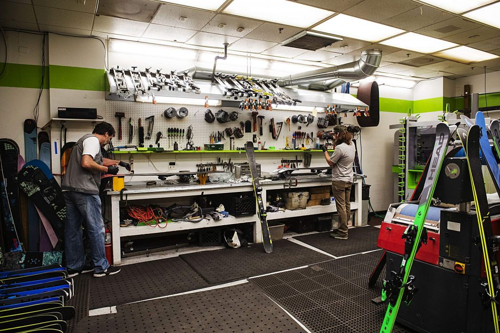 John Norman and Jamie Capel apply Phantom to the bottom of rental skis before the season opens in the tune shop at Aspen Highlands on Wednesday.