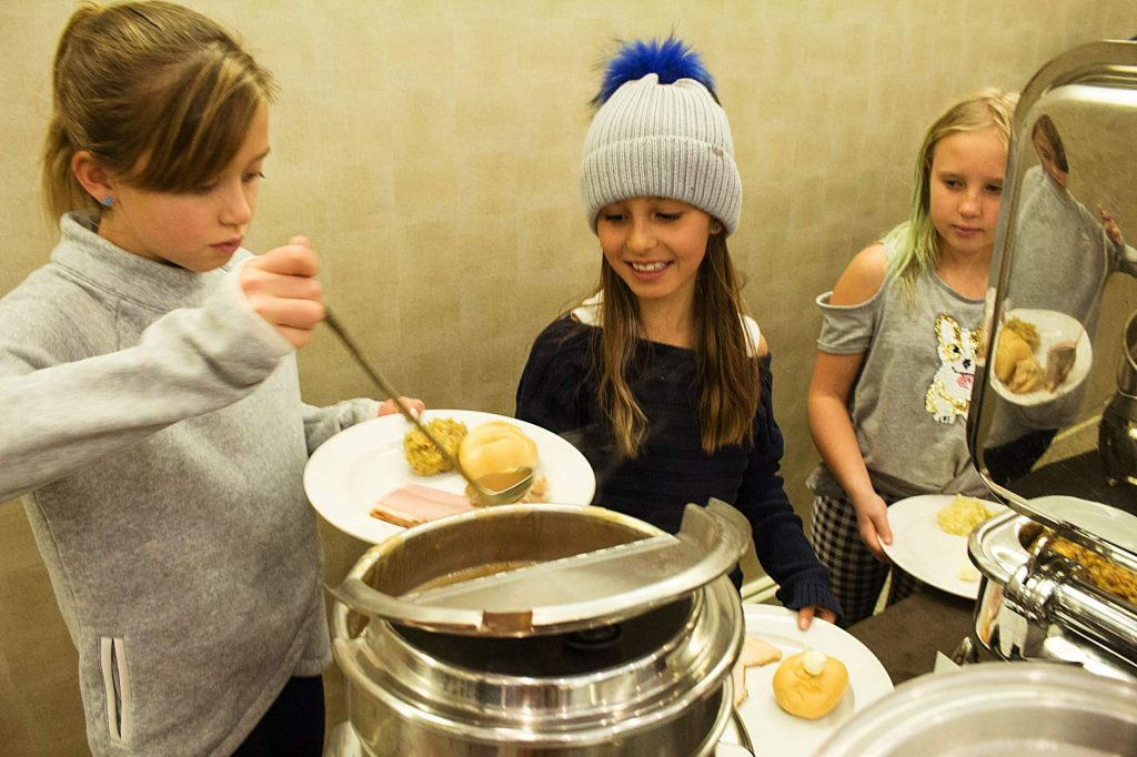 Allessa Oliver, 9, Gigi Trani, 10, and Emma Jane Mallory, 10, fill their plates during the John Bemis Community Potluck Dinner on Sunday in Snowmass Village.
