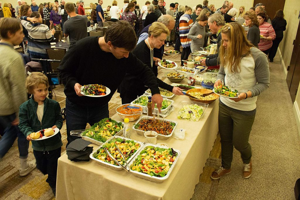 Dozens of locals make their way through the salad line of the John Bemis Community Potluck Dinner in Snowmass on Sunday, Nov. 24, 2019.