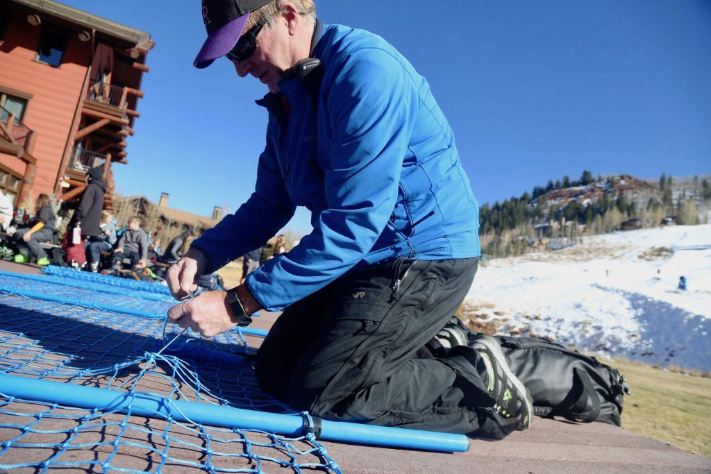 Pat Callahan, the Aspen Valley Ski and Snowboard Club's race director, fixes some of the netting used to setup the ski courses at the Stapleton Training Center on Sunday, Nov. 10, 2019, at Aspen Highlands. The venue opened on Saturday, Nov. 9, the earliest opening it its short six-year history. (Photo by Austin Colbert/The Aspen Times)