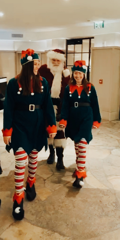 Elves Janelle Patrick and Ava Applebaum lead Santa through the lobby at The Little Nell Tree Lighting.