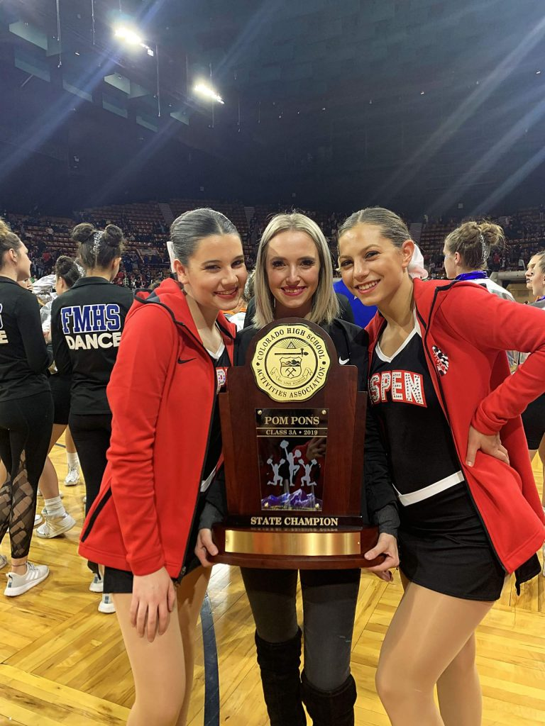 Aspen High School dance team captains Juliana Nickell, left, and Louise Lipsey, right, pose with coach Maddy Miller after the team won the Class 3A poms state championship on Saturday in Denver.
