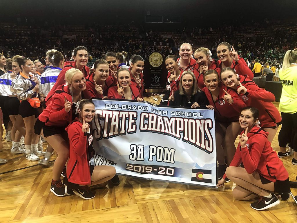 The Aspen High School dance team celebrates with the trophy and banner after winning the Class 3A poms state championship on Saturday at the Denver Coliseum. It's the first state title in program history.